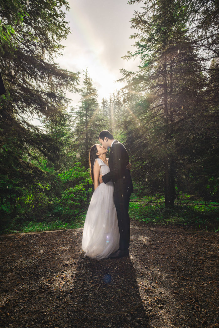bride and groom at moraine lake with rainbow in sky
