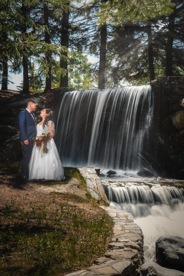 bride and groom posing against waterfall