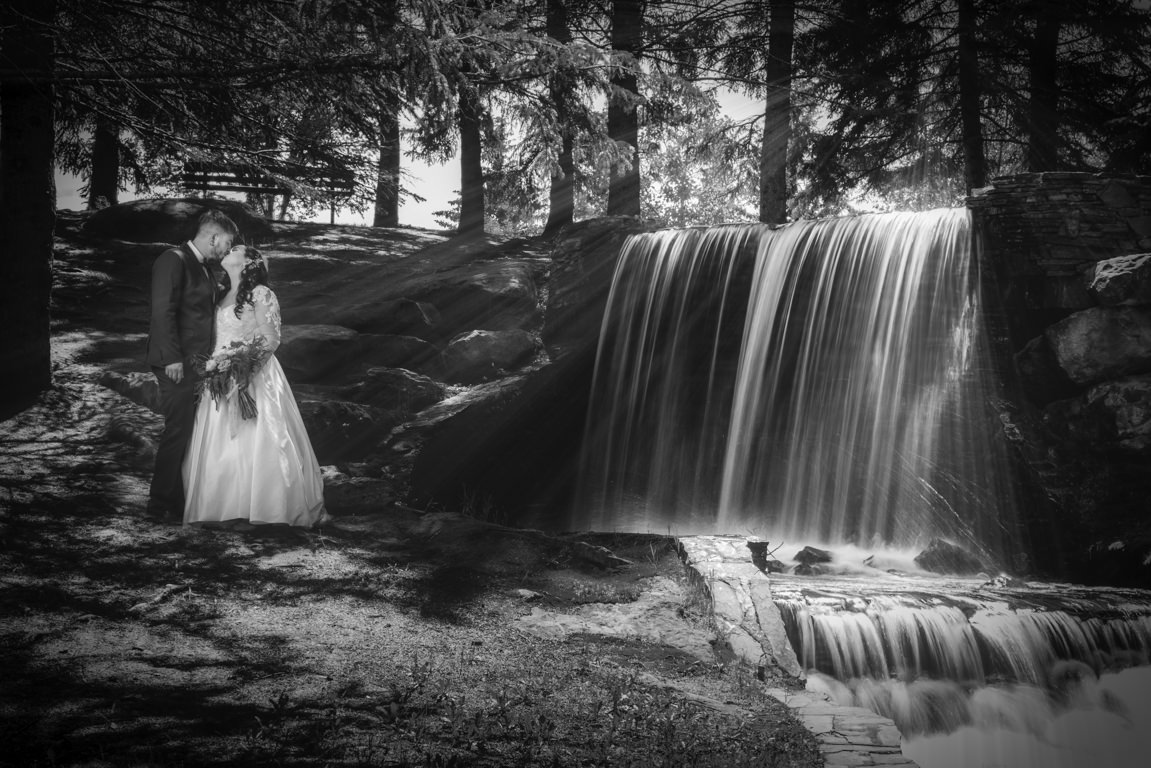 bride and groom kissing with waterfall in the background