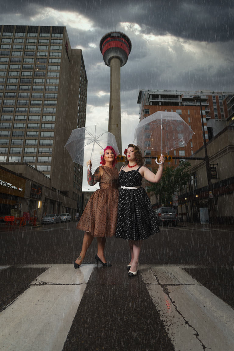pin up girls with umbrellas at the base of the calgary tower