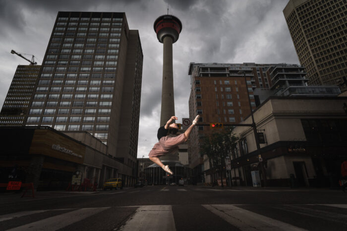 Clara Kearl jumping in front of Calgary tower