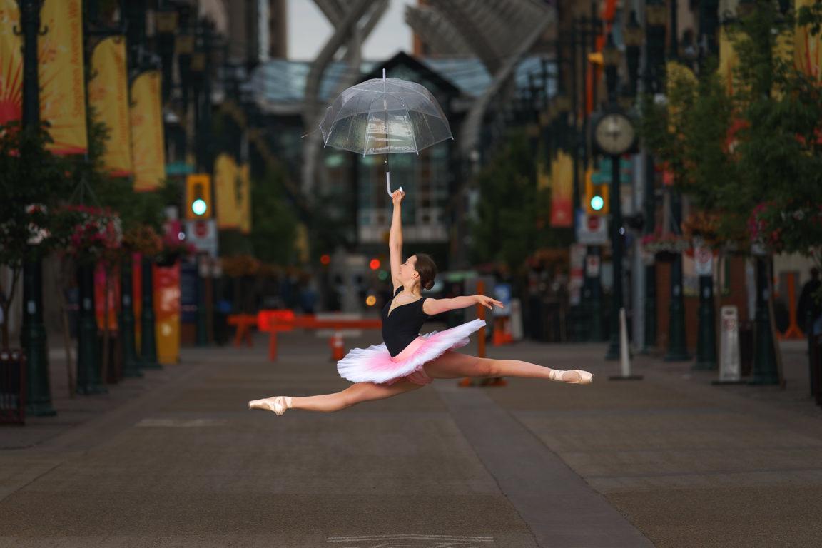 Clara Kearl jumping with umbrella on Stephen Avenue