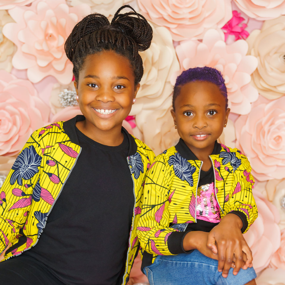 portrait of 2 young kids in front of a floral wall