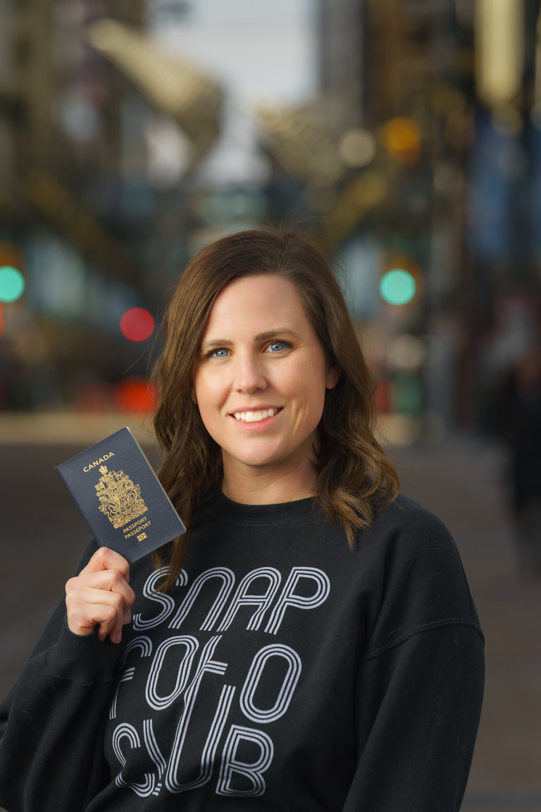 woman holding passport on stephen avenue in downtown Calgary
