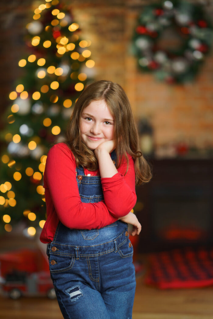 young girl posing in front of Christmas tree