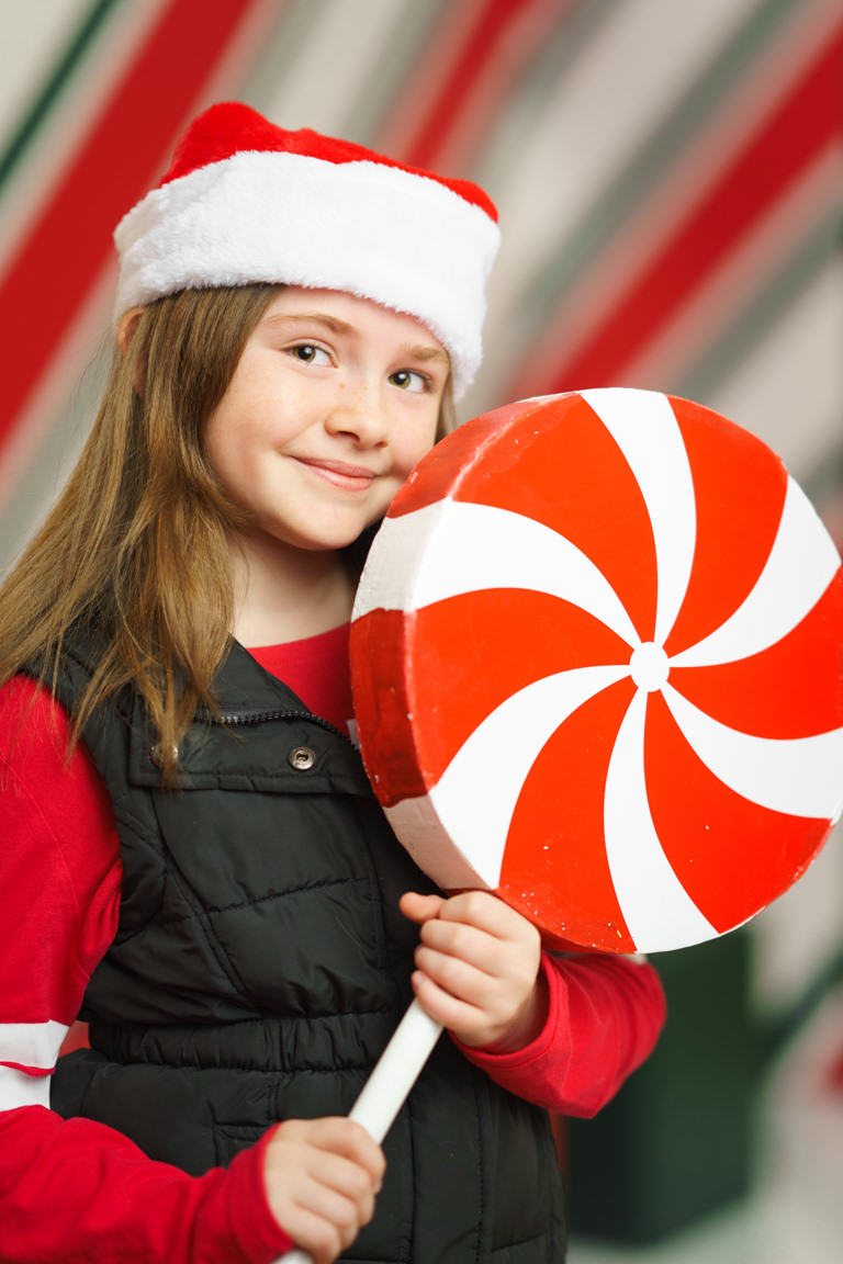 young girl posing in front of candy cane display