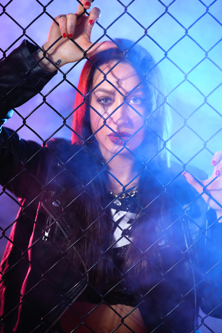 model posing behind fence with smoke