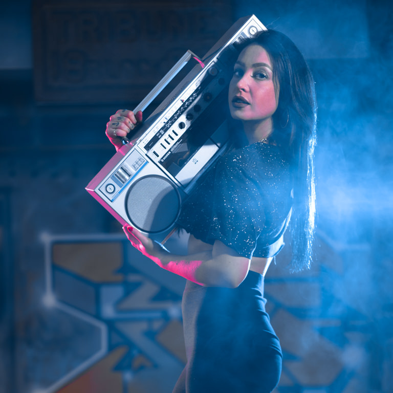 model posing behind fence with boombox