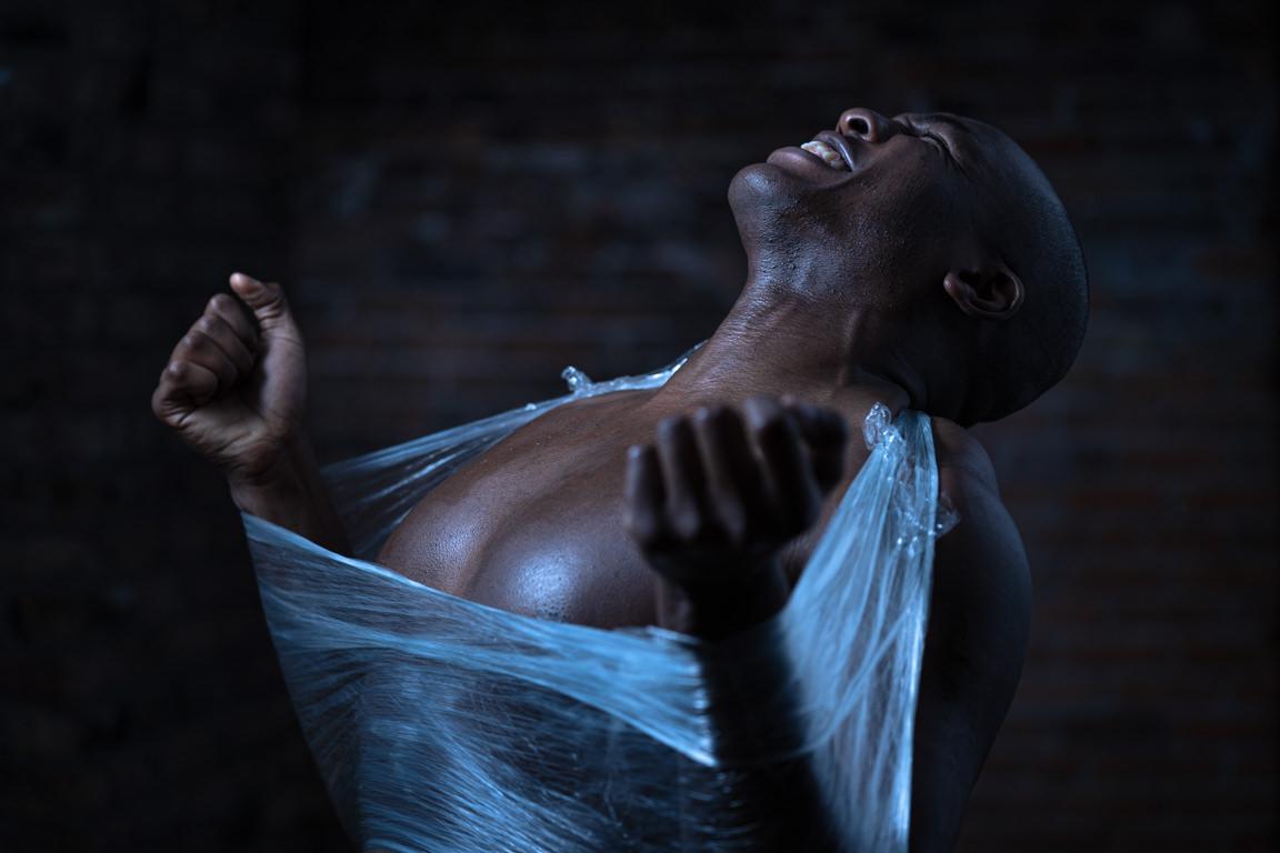 black man breaking out of saran wrap