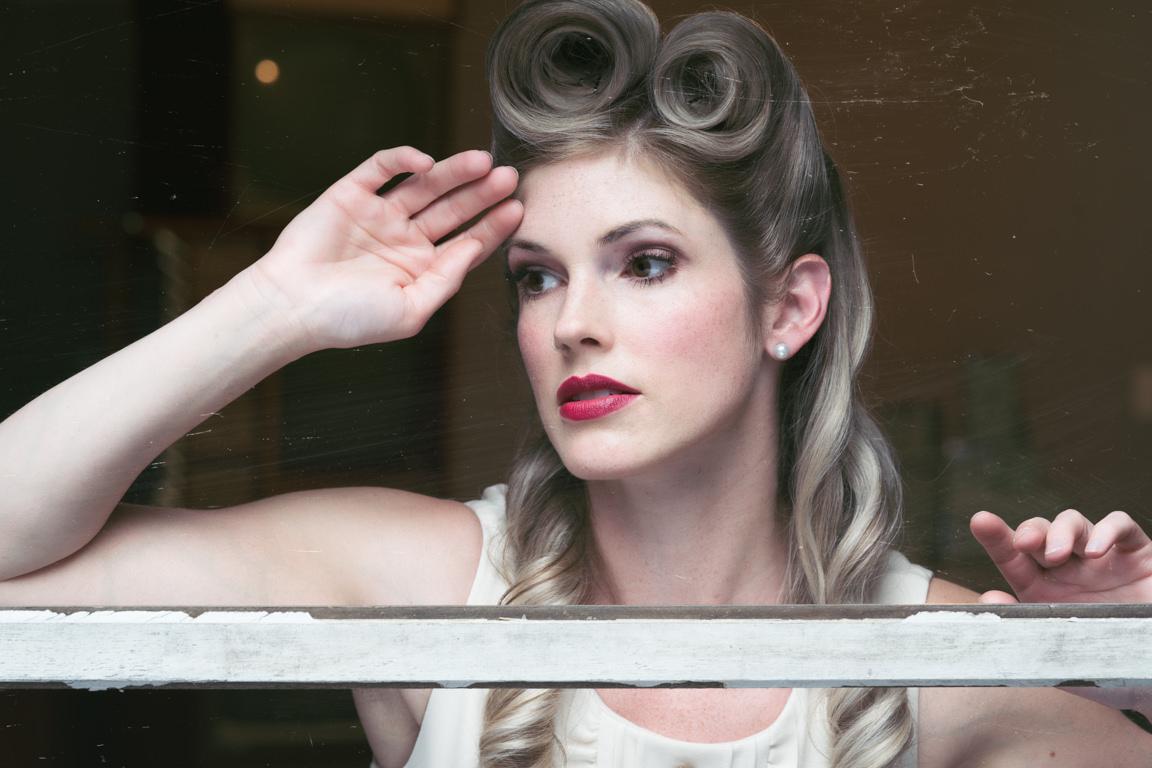 40's model posing through window in kitchen
